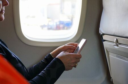 Montreal, Canada - October 27, 2019 - A passenger using a smartphone inside the plane before take off