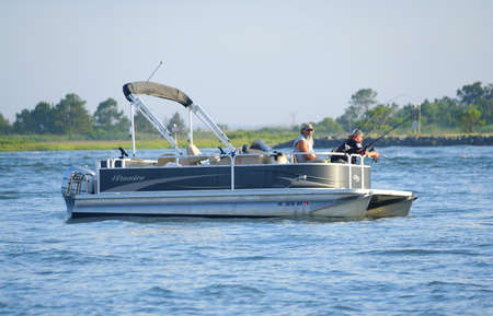 Bethany Beach, Delaware, U.S.A - June 20, 2020 - Anglers on the pontoon boat fishing for flounder near Indian River Inlet in the summer