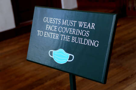 Williamsburg, Virginia, U.S.A - June 30, 2020 - The door sign asking visitors to wear mask before entering the building 新闻类图片