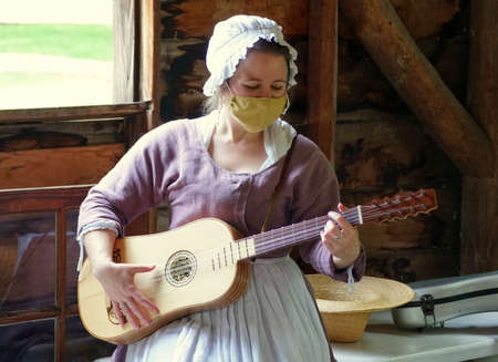 Williamsburg, Virginia, U.S.A - June 30, 2020 - A lady in colonial costume performing a guitar and wearing a mask