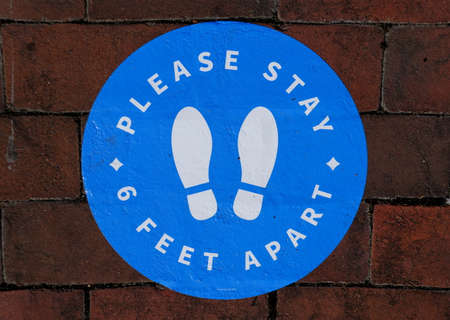 Williamsburg, Virginia, U.S.A - June 30, 2020 - The sticker on the brick walkway asking the customers to stay 6 feet apart