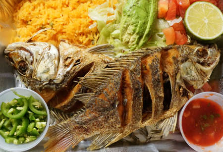 Pescado Frito, a Mexican dish with fried tilapia, yellow rice and salad