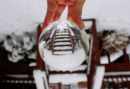 Wooden stairs with snow captured through a crystal lens ball