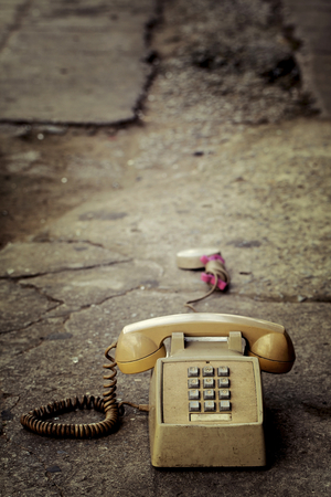 Dirty old phone on the floor and old concrete. photo