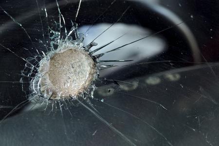 black hole: close up shot of broken glass of car window.