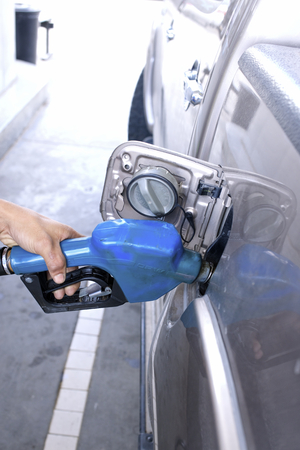 Blue fuel nozzle in pouring to car. photo