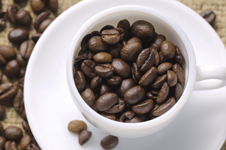 upperdeck view: cup of coffee with coffee beans.