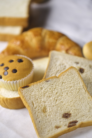 upperdeck view: assortment of baked bread and rolls arranged on coarse textured, woven fabric Stock Photo