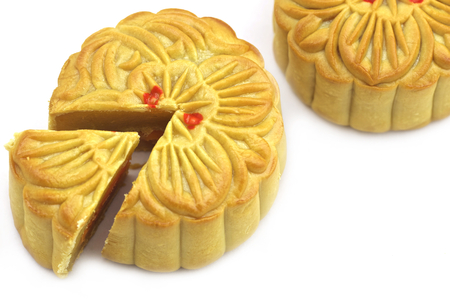 chinese cuisine: Chinese Mooncake isolated over white background, the Chinese words on the mooncake means yolk.