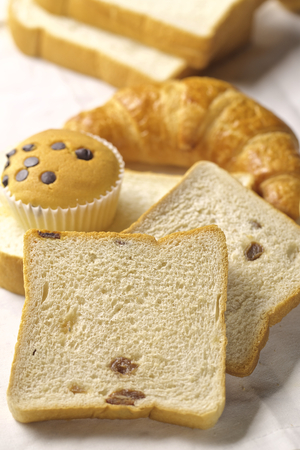 baked bread: assortment of baked bread and rolls arranged on coarse textured, woven fabric Stock Photo