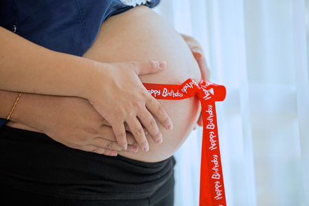 bow belly: Pregnant woman with red ribbon