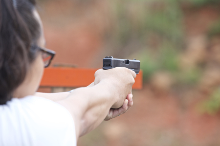Man holding a pistol in his hands, ready to shoot