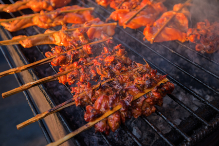 Grilling spiced chicken, roasted chicken at street food vendor market, Thai style food.