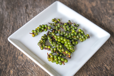 Black pepper is placed in a white plate on a wooden table. Stock Photo