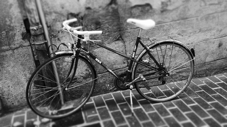 In a tiled lane, an old bike posed against a wall