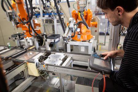 Man programming robot in automotive industrial, professional programmer