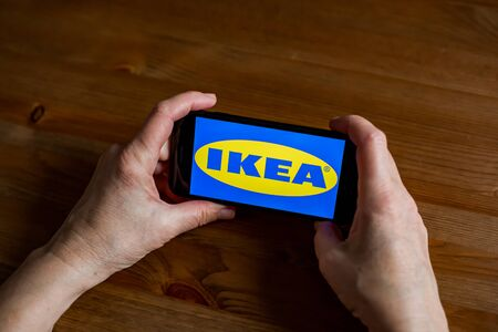 Ikea logo sign application screen on mobile phone online retail service, hands on