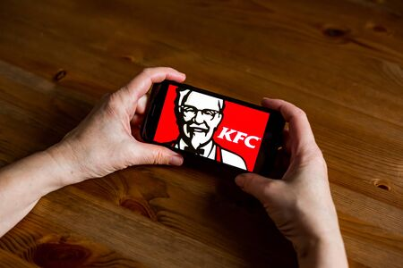 Kfc logo sign application screen on mobile phone online retail service, hands on Editorial