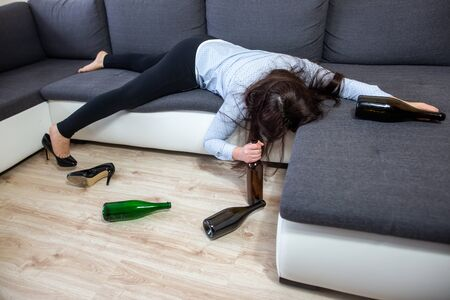 Drunk woman lying on the sofa with kind of wine bottles, alcoholism concept, alcohol addiction Reklamní fotografie