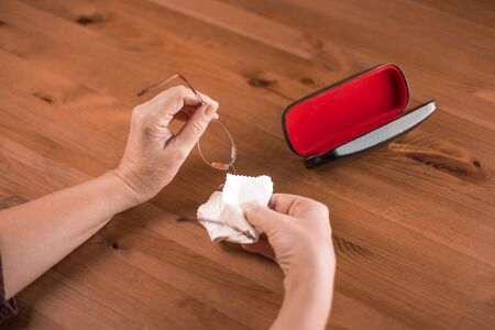 Dirty eyeglasses, woman hand thoroughly cleaning eyeglasses by a cloth,