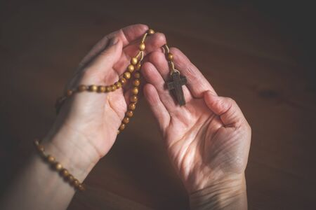 Woman praying with wooden rosary, religion concept