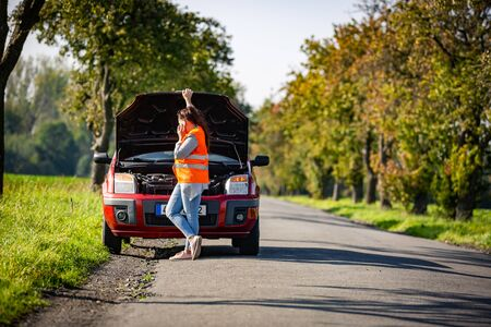 Pretty young woman by the roadside after her car has broken down, calling assistence Stock Photo