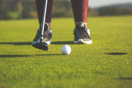 Hübsche junge Frau, die Golf auf Trainingsplatz spielt, schlägt den Golfball in das Loch Standard-Bild