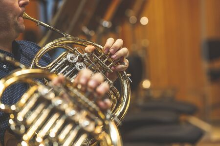 Man playing on french horn during philharmonic concert, art