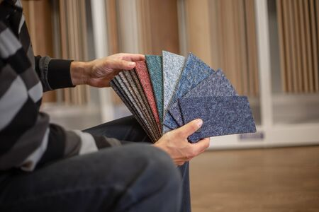 Man choosing the rigt colour of carpet for his new apartment in floor studio, flooring