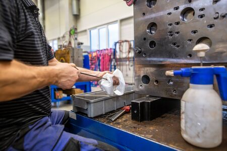 Engineer doing maintenance on the injection mold after production, cleaning injection mold