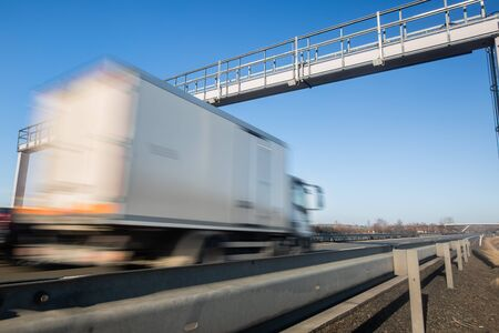 Truck passing through a toll gate on a highway, highway charges, motion blurred image