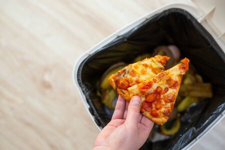 Stop wasting food, Woman hand throwing some food, pizza pieces to the bin, trash, food concept Stock Photo