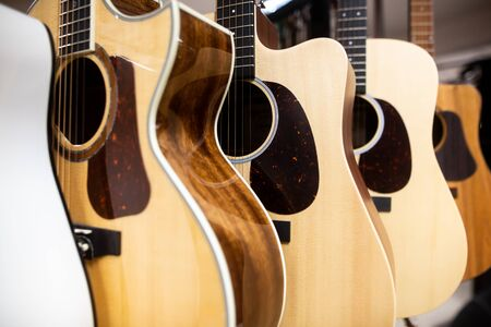 Close up of classic guitar drapped in a row in a huge musical shop, instrument shop, instrument concept 免版税图像