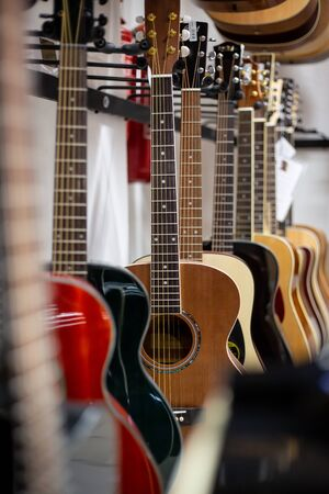 Close up of classic guitar drapped in a row in a huge musical shop, instrument shop