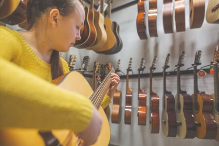 Young woman trying, buying new guitar in a instrument shop, instrumental concept