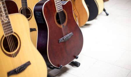 Close up of wooden guitar in a row in instrument shop