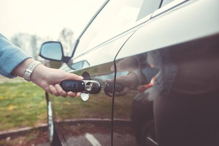 Woman unlocking, opening the car by the vehicle key, safety concept, transportation