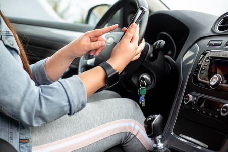 Woman driver using a mobile, smartphone during driving her car, dangerous concept