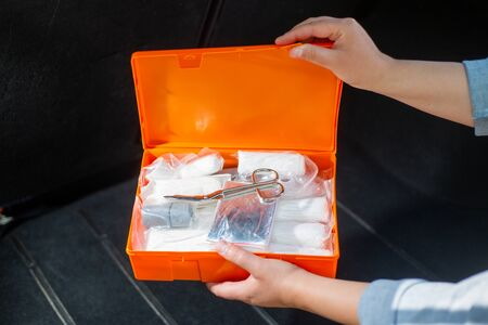 Woman opening compulsory car first aid kit with kind of fisrt aid equipment, healthcare concept