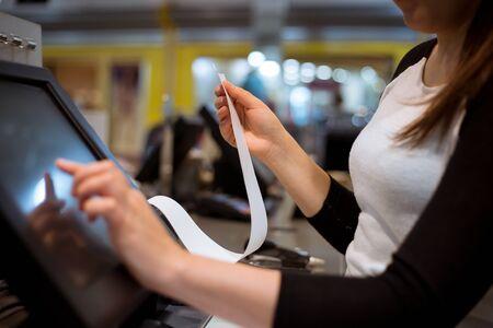 saleswoman, shopgirl printing a receipt, invoice for a customer, sales time, discount period Banco de Imagens