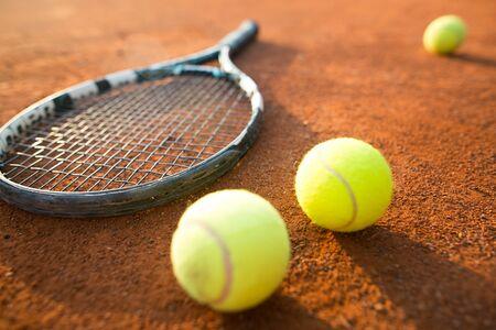 Vue rapprochée de la raquette de tennis et des balles sur le court de tennis en terre battue, sport récréatif, temps libre