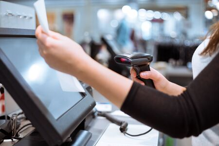 Young woman hands scaning, entering discount, sale on a receipt, touchscreen cash register, POS, finance concept
