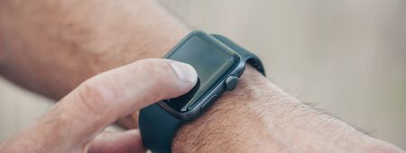 Macro concept of man clicking, pointing on screen of his generic design smart watch, blurred background