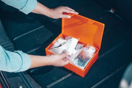 Woman opening compulsory car first aid kit with kind fisrt aid equipment, health care concept