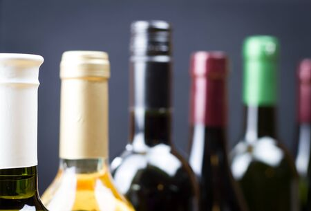 Close up of wine bottles in a row isolated on a gray background