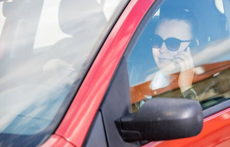 Pretty young woman using a smart phone, mobile while driving a car, transportation concept