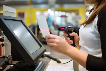 Young woman hands scaning, entering discount, sale on a receipt, touchscreen cash register, POS, finance concept Фото со стока
