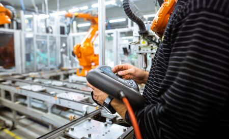 Engineer setting up automatic robot arms in the smart factory, automotive industry, industrial concept