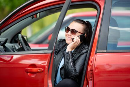Young woman calling by mobile, smartphone in the car parking lot, transportation concept 版權商用圖片