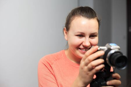 Young female blogger recording a video for her subscribers by a professional camera, vlog